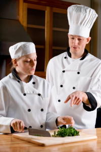 A chef teaching a culinary student proper knife techniques. Shallow dof, focus on the teaching chef.