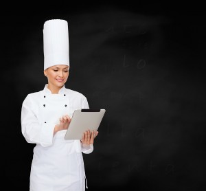 cooking, technology and food concept - smiling female chef with