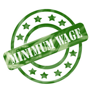 A green ink weathered roughed up circle and stars stamp design with the words MINIMUM WAGE on it making a great concept.