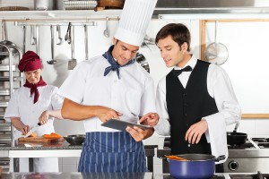 Chef and waiter using digital tablet with female chef working in