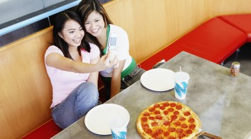 Two teenage girls taking picture with cell phone at pizza restau