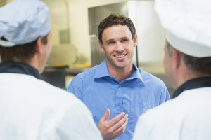 Young smiling manager talking to the staff standing in a kitchen