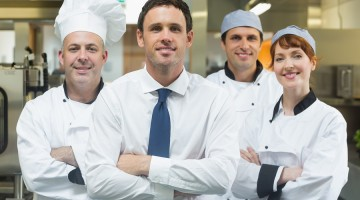 Restaurant manager standing in front of team of chefs smiling at